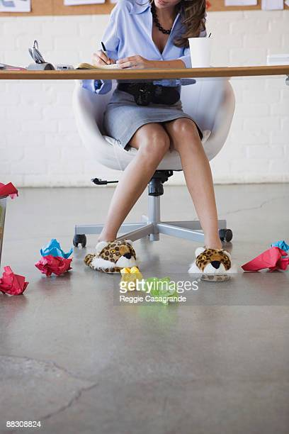 frustrated businesswoman sitting at desk wearing fuzzy slippers - animal representation stock pictures, royalty-free photos & images