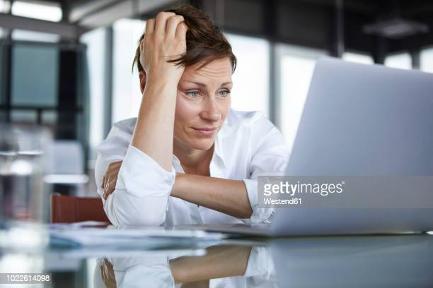 frustrated businesswoman sitting at glass table in office looking at laptop - disappointment stock pictures, royalty-free photos & images