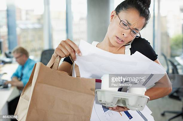 frustrated businesswoman talking on cell phone with paperwork and coffee - multi tasking stock pictures, royalty-free photos & images