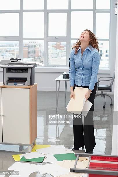 Frustrated Businesswoman with Dropped Papers