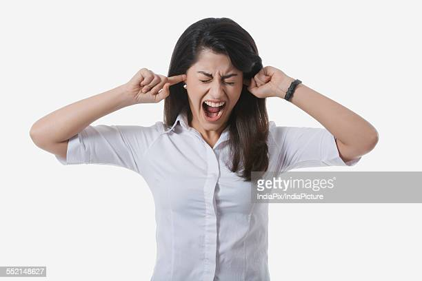 Frustrated businesswoman with fingers in ears yelling against white background
