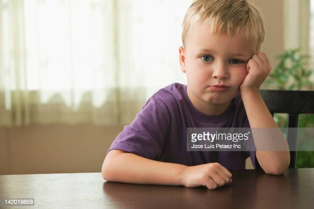 Frustrated Caucasian boy with head in  hands