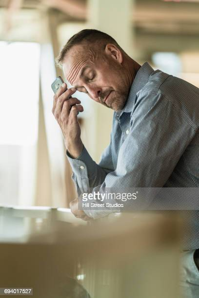 Frustrated Caucasian businessman holding cell phone