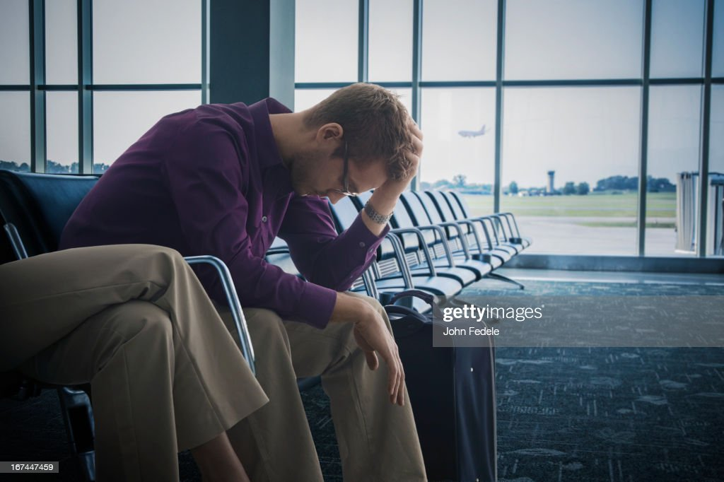 Frustrated Caucasian man sitting airport : Stock Photo