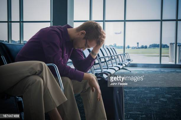 Frustrated Caucasian man sitting airport