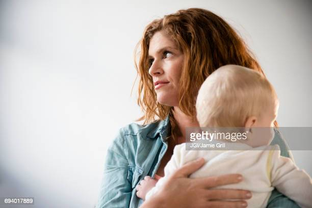 frustrated caucasian mother holding baby son - postpartum depression stock pictures, royalty-free photos & images