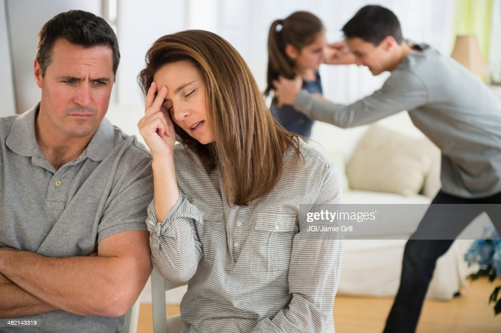 Frustrated Caucasian parents listening to children fight : Stock Photo