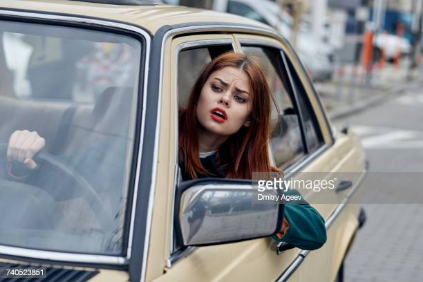 Frustrated Caucasian woman leaning on door driving car