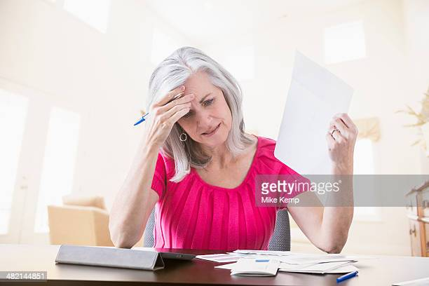 Frustrated Caucasian woman paying bills online