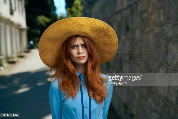 frustrated caucasian woman wearing hat near stone wall - frowning stock pictures, royalty-free photos & images