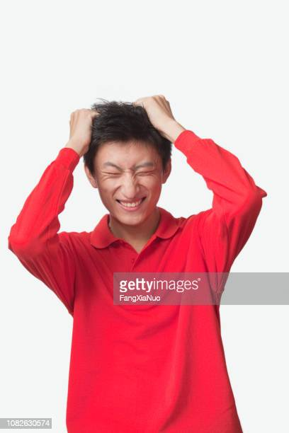 frustrated chinese man with head in hands - hysteria stock pictures, royalty-free photos & images