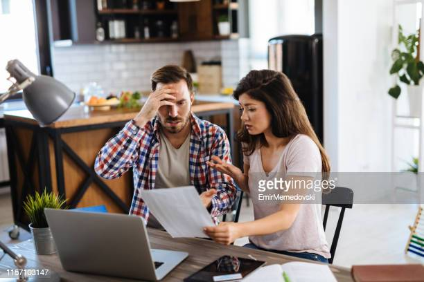 frustrated couple checking bills at home using laptop - husband stock pictures, royalty-free photos & images