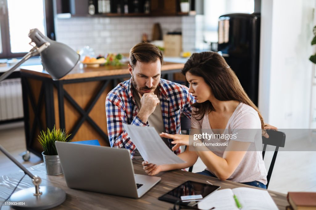 Frustrated couple checking bills at home using laptop : Stock Photo