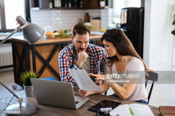 frustrated couple checking bills at home using laptop - financial bill stock pictures, royalty-free photos & images