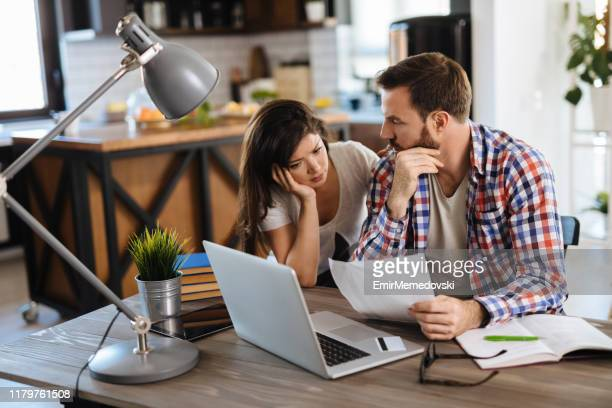 frustrated couple checking bills at home using laptop - mortgage loan stock pictures, royalty-free photos & images