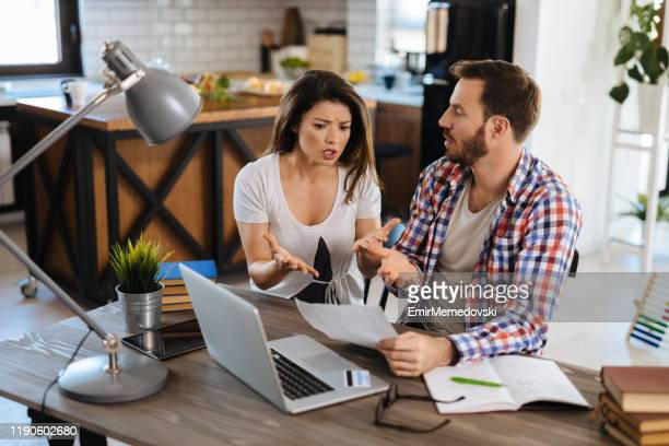 frustrated couple checking bills at home using laptop - bank statement stock pictures, royalty-free photos & images