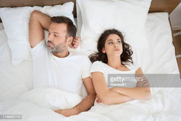 frustrated couple lying in bed - couple lit photos et images de collection