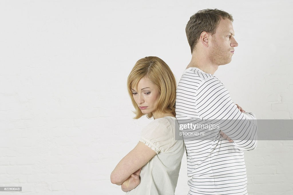 Frustrated couple standing back to back : Stock Photo