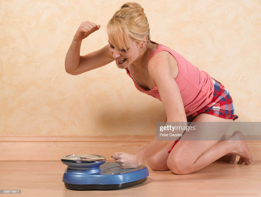 Frustrated Dieter hitting scales : Stock Photo