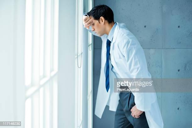 Frustrado médico apoyarse en la ventana