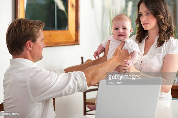 Frustrated father giving a crying baby to his wife