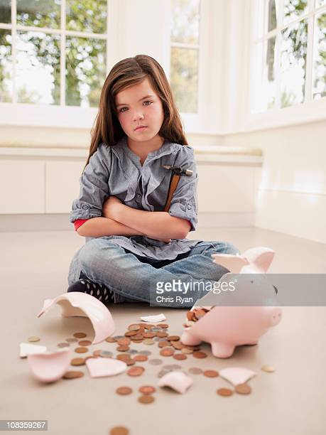 Frustrated girl sitting with broken piggy bank