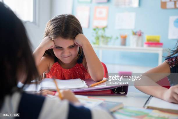 frustrated girl staring at notebook in school - bemühung stock-fotos und bilder