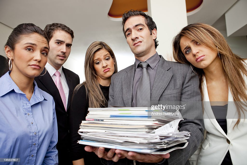 Frustrated Hispanic business people with pile of paperwork : Stock Photo