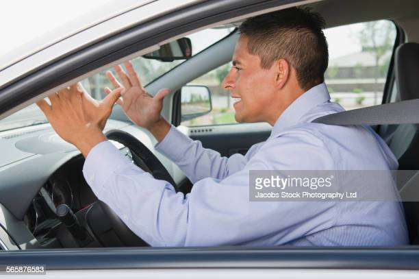 Frustrated Hispanic businessman driving in traffic