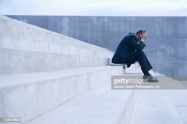 Frustrated Hispanic businessman sitting on steps