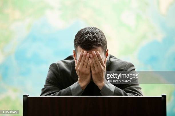 frustrated hispanic businessman standing at podium - head in hands stock pictures, royalty-free photos & images