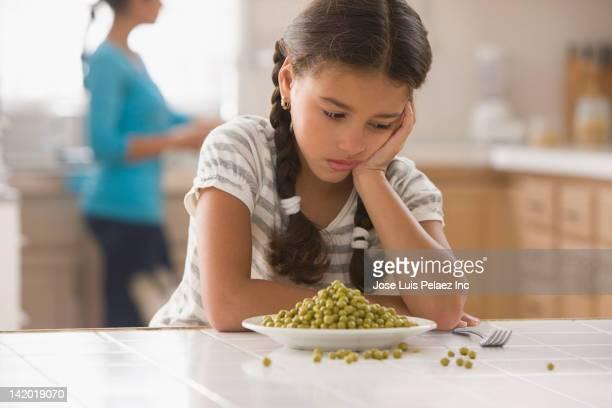 frustrated hispanic girl sitting with bowl of peas - afkeer stockfoto's en -beelden