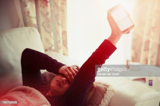 Frustrated Indian woman laying on sofa holding glowing cell phone