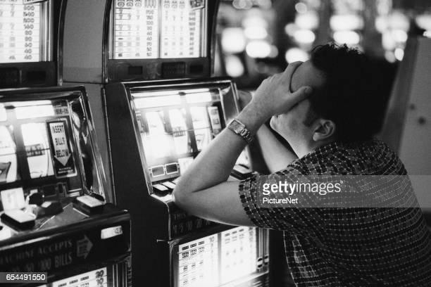 frustrated man at slot machine - ongeduldig stockfoto's en -beelden