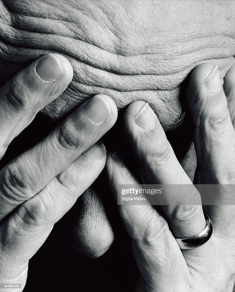 Frustrated man burying face in hands : Stock Photo