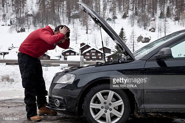Frustrated man checking car engine