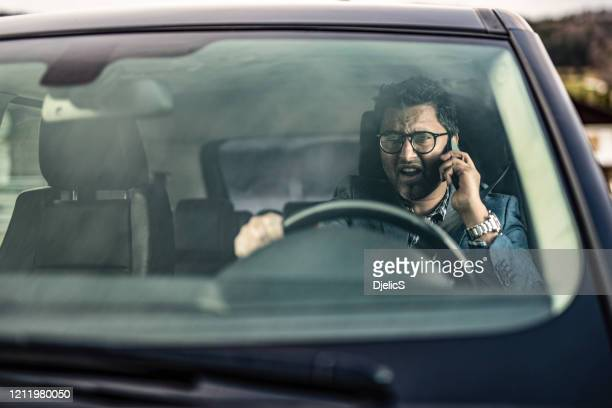 frustrated man driving and talking on phone. - social issues stock pictures, royalty-free photos & images