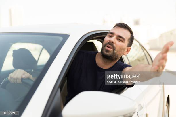 Frustrated Man Gesturing Through Window While Traveling In Car