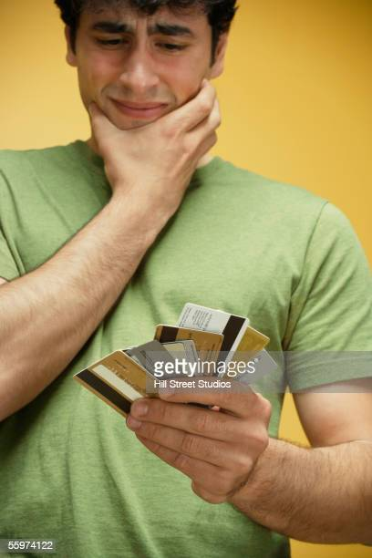Frustrated man holding credit cards