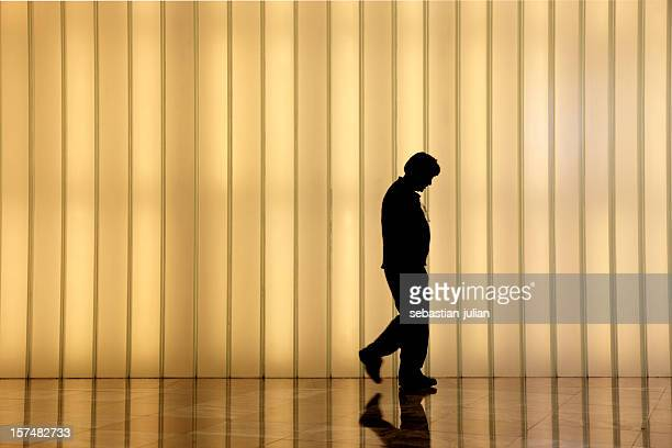 frustrated man in front of modern light wall