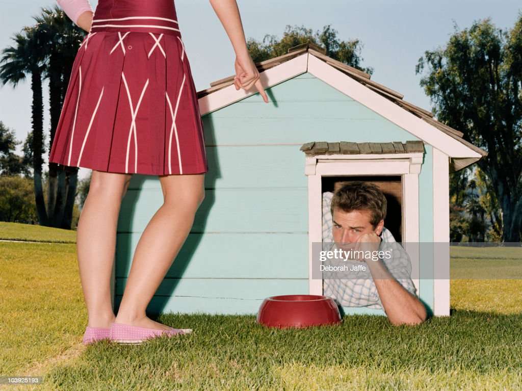 Frustrated man laying in doghouse : Stock Photo