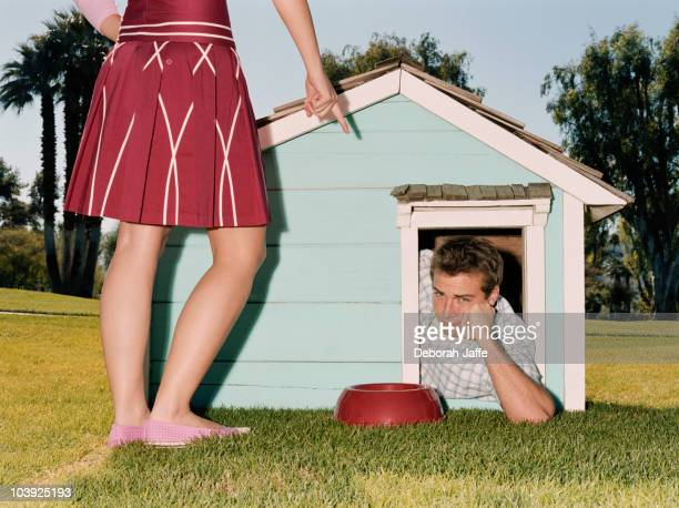 frustrated man laying in doghouse - women dominating men stock photos and pictures