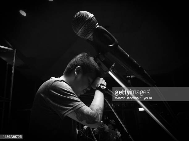 frustrated man leaning on microphone - musician stock pictures, royalty-free photos & images
