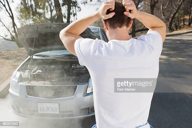 frustrated man looking at smoking car engine - hands behind head stock pictures, royalty-free photos & images