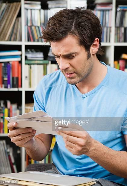 Frustrated Man Looking Through Bills