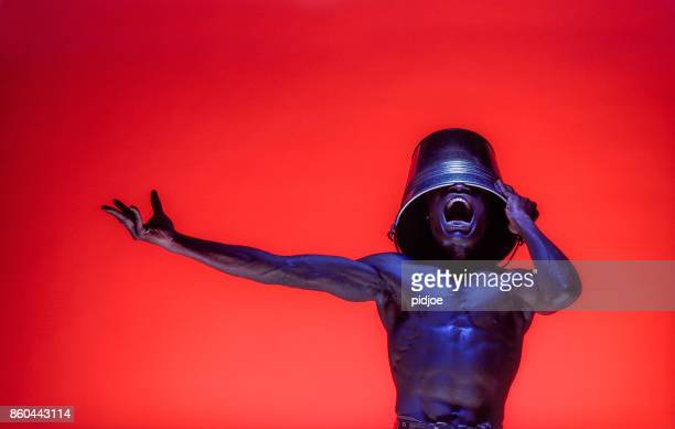 Frustrated man of African decent Furious Screaming against a deep red background