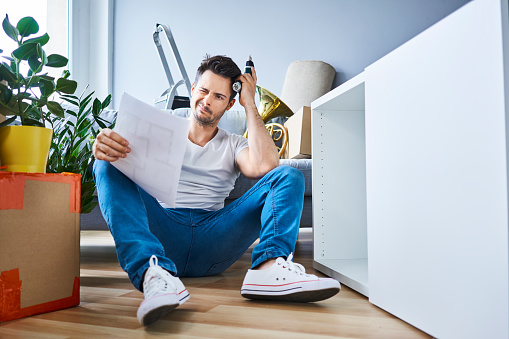 Frustrated man reading instructions while assembling furniture in new apartment - gettyimageskorea