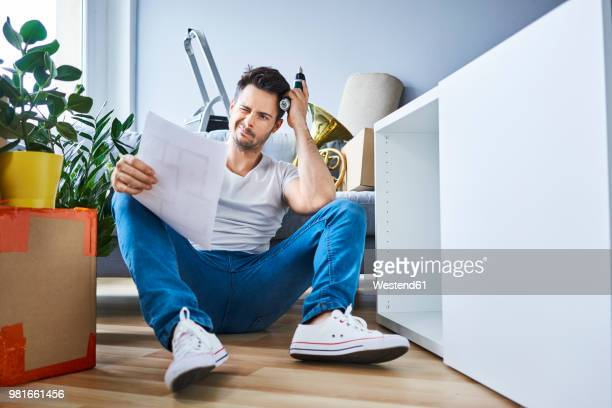 frustrated man reading instructions while assembling furniture in new apartment - diy stock pictures, royalty-free photos & images