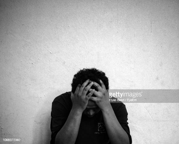 frustrated man sitting against wall - 絶望 ストックフォトと画像