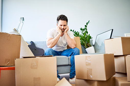 Frustrated man sitting on couch surrounded by cardboard boxes - gettyimageskorea